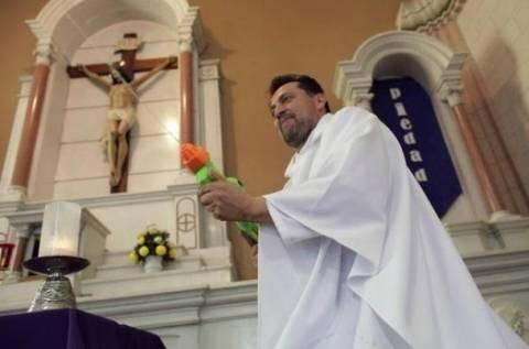 Απίστευτο: Ιερέας-μπάτμαν ψεκάζει αγιασμό με...νεροπίστολο (pics)