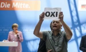 Δημοψήφισμα: Η Μέρκελ απαντά στα… ελληνικά σε ακτιβιστές του «όχι» που τη διέκοψαν (video)