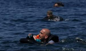 Συγκλονιστικές φωτογραφίες: Πρόσφυγας κολυμπάει με μωρό στην αγκαλιά του