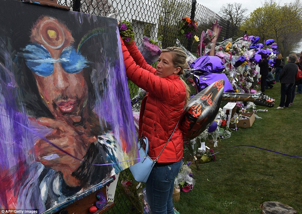 3372AE0700000578 3554472 A Prince fan attaches flowers to a memorial wall as she pays her a 11 1461362199355