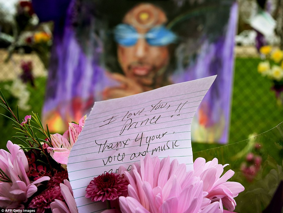 3372CCA000000578 3554472 A Prince fan holds flowers outside the Paisley Park compound in a 13 1461362199357