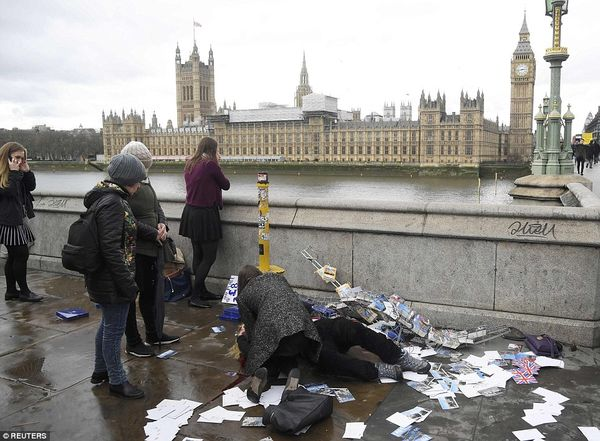 3E87554E00000578 4338998 A woman leans down on Westminster Bridge to help another woman w a 1 1490219423721