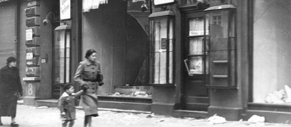 Mother and chiled passing by destroyed shop fronts. THe Wiener Library