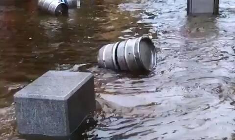 Οι δρόμοι έγιναν ποτάμια από τις πλημμύρες και γέμισαν με βαρέλια μπίρας