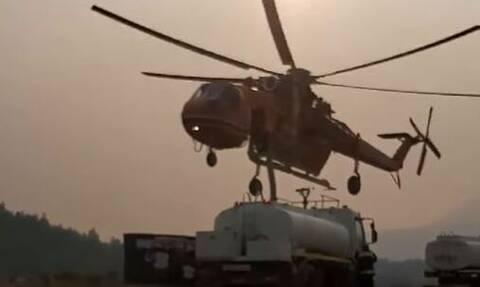 Στιγμιότυπο από τη μάχη με τις φλόγες στα Βίλια: Ελικόπτερο εφοδιάζεται από υδροφόρα